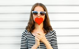 Portrait close-up woman kissing red heart shaped lollipop or hides her lips on white wall. Background stock image