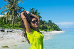 Portrait close up of young beautiful asian girl standing on the beach and fixing her hair Royalty Free Stock Photography