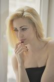 Portrait close up of young beautiful blonde woman near window Stock Photography