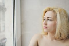 Portrait close up of young beautiful blonde woman near window Royalty Free Stock Images