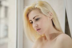 Portrait close up of young beautiful blonde woman near window Stock Photos