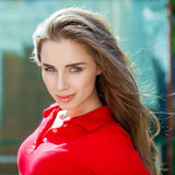 Portrait close up of young beautiful brunette woman. In red polo, summer outdoors Royalty Free Stock Photos