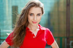 Portrait close up of young beautiful brunette woman. In red polo, summer outdoors Stock Image