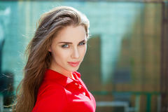 Portrait close up of young beautiful brunette woman. In red polo, summer outdoors Royalty Free Stock Image