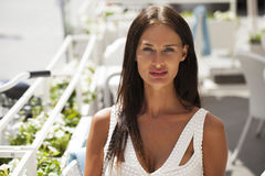 Portrait close up of young beautiful brunette woman. In white dress, summer street Stock Image