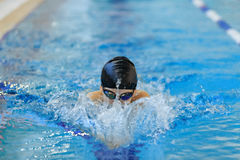 Portrait of close-up young girl in goggles and cap swimming butterfly stroke style in the blue water pool. Royalty Free Stock Photos