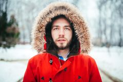 Portrait, close-up of a young stylish man with a beard dressed in a red winter jacket with a hood and fur on his head stands again. St the background of a snow Stock Image