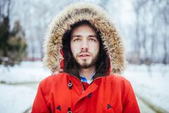 Portrait, close-up of a young stylish man with a beard dressed in a red winter jacket with a hood and fur on his head stands again. St the background of a snow Royalty Free Stock Image