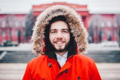 Portrait, close-up of a young stylishly dressed man smiling with a beard dressed in a red winter jacket with a hood and fur on his. Portrait, close-up of young Royalty Free Stock Photography