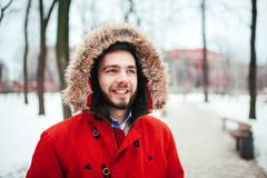 Portrait, close-up of a young stylishly dressed man smiling with a beard dressed in a red winter jacket with a hood and fur on his. Head. Winter and frost theme Stock Photos