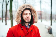 Portrait, close-up of a young stylishly dressed man smiling with a beard dressed in a red winter jacket with a hood and fur on his. Head. Winter and frost theme Stock Image