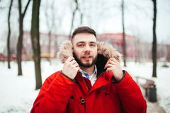 Portrait, close-up of a young stylishly dressed man smiling with a beard dressed in a red winter jacket with a hood and fur on his. Head. Winter and frost theme Royalty Free Stock Images
