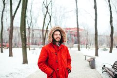 Portrait, close-up of a young stylishly dressed man smiling with a beard dressed in a red winter jacket with a hood and fur on his. Head. Winter and frost theme royalty free stock photo