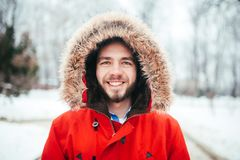 Portrait, close-up of a young stylishly dressed man smiling with a beard dressed in a red winter jacket with a hood and fur on his royalty free stock images