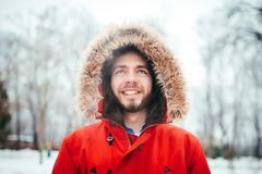 Portrait, close-up of a young stylishly dressed man smiling with a beard dressed in a red winter jacket with a hood and fur on his. Portrait, close-up of young Stock Photo