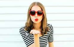 Portrait close-up young woman blowing red lips sending sweet air kiss on white wall. Background stock images