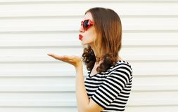 Portrait close-up young woman blowing red lips sending sweet air kiss on white wall. Background royalty free stock image