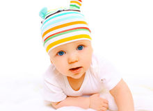 Portrait closeup of baby in colorful hat crawls on a white Royalty Free Stock Image