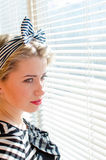 Portrait of closeup on beautiful blond young woman pinup girl having fun happy smiling & looking sensually through windows Royalty Free Stock Photos