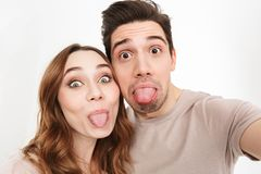 Portrait closeup of joyful couple hugging and making faces with. Sticking tongues out on camera while taking selfie isolated over white background Royalty Free Stock Photography