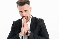 Portrait closeup of serious focused businessman wearing black ja. Cket putting palms together and wishing luck isolated over white background Royalty Free Stock Image
