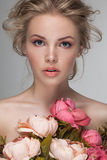 Portrait closeup of a young beautiful blonde woman with fresh flowers. Stock Photos