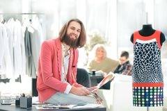 Portrait of a clothing designer sitting on a Desk in the Studio stock photos