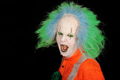 Portrait of clown. Half body portrait of clown with white face and green hair making scary face, isolated on black background royalty free stock photo