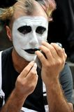Portrait of a clown street artist in Florence, Italy putting makeup on before a street show