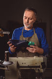 Portrait of a cobbler with footwear. Mature master holding almost finished shoe in his hands in the atelier royalty free stock photography