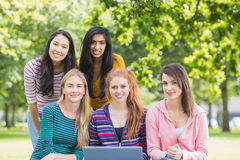 Portrait of college girls with laptop in park Stock Photos