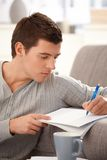 Portrait of college guy taking notes. Portrait of college student guy taking notes, studying at home Stock Photography