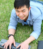Portrait college student with laptop. College student with laptop laying on the grass smilling Royalty Free Stock Image