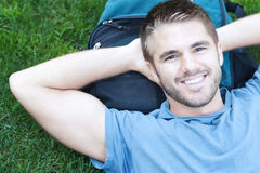 Portrait of a college student lying in grass Royalty Free Stock Images