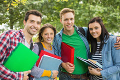 Portrait of college students with bags and books in park Stock Photo