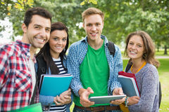 Portrait of college students with bags and books in park. Group portrait of young college students with bags and books standing in the park Royalty Free Stock Photo