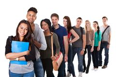Portrait of college students standing in a line. Portrait of multiethnic college students standing in a line over white background royalty free stock image