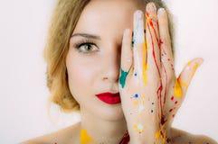 Portrait coloré de femme en peinture avec la main près des yeux images libres de droits