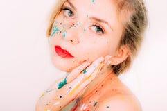 Portrait coloré de femme en peinture avec la main près du visage photographie stock libre de droits
