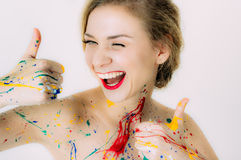 Portrait coloré de femme en peinture avec les lèvres rouges composant des pouces photographie stock libre de droits
