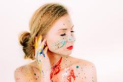 Portrait coloré de jeune femme en peinture avec les lèvres rouges photos stock