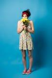 Portrait coloré de la jeune fille drôle posant sur le mur bleu photos stock