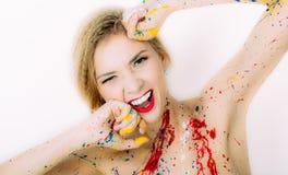 Portrait coloré riant de femme avec des mains près du visage dans le pai image stock