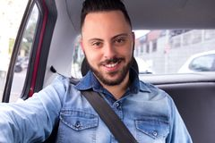 Portrait of commuter student man smiling and using taxi cab service in back seat of car. Concept of commute, transport service, m royalty free stock photo