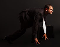 Portrait of a competitive businessman at starting position. On black.Side view Royalty Free Stock Photo