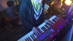 Composer records a new album, playing a synthesizer, jam session