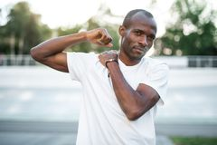 Focused male doing workout outdoor. Portrait of concentrated african man gesticulating hands while warming up before training on open air Royalty Free Stock Image