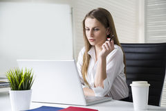 Portrait of a concentrated and beautiful businesswoman wearing a white blouse and looking at her laptop screen. Royalty Free Stock Image