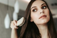 Focused woman combing long dark hair indoor stock images