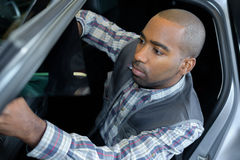 Portrait concentrated handsome mechanic checking car door Royalty Free Stock Photo